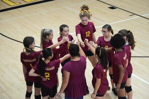 girl volleyball players in a huddle..hands together in unity.