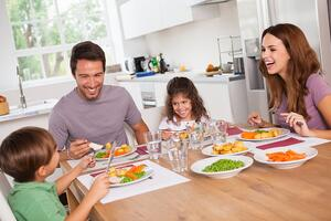 Family laughing, being thankful, sharing, around a meal in kitchen